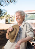 Smiling senior lady leaning against a vintage pickup truck Royalty Free Stock Image