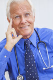 Smiling Senior Male Doctor With Stethoscope. A happy smiling senior male doctor sitting at a desk in an office wearing a shirt, tie and stethoscope stock photos