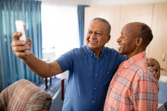 Smiling senior male friends taking selfie from mobile phone. At nursing home Stock Image