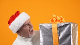 Smiling senior male holding huge heavy present box, holiday surprise, greeting. Stock footage stock footage