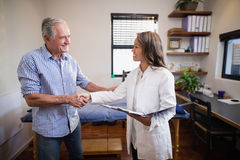 Smiling senior male patient and female therapist shaking hands against window stock photo