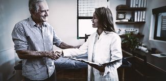 Smiling senior male patient and female therapist shaking hands against window royalty free stock photo