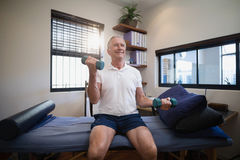 Smiling senior male patient lifting dumbbells while sitting on bed Royalty Free Stock Photos