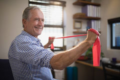 Smiling senior male patient pulling red resistance band Stock Image
