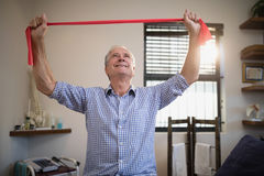 Smiling senior male patient pulling red resistance band while looking up Royalty Free Stock Images