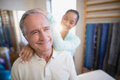 Smiling senior male patient receiving neck massage from female therapist. At hospital ward Royalty Free Stock Photo