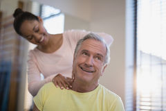 Smiling senior male patient receiving neck massage from therapist. At hospital ward Stock Photography