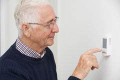 Smiling Senior Man Adjusting Central Heating Thermostat. Senior Man Adjusting Central Heating Thermostat Stock Photography