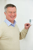Smiling Senior Man Adjusting Central Heating Thermostat. Smiling Senior Man Adjusts Central Heating Thermostat Stock Photo