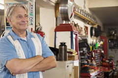 Smiling senior man in automobile workshop Stock Image