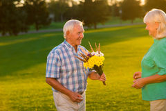 Smiling senior man with bouquet. Royalty Free Stock Photo