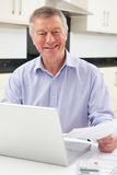 Smiling Senior Man Checking Home Finances Stock Photo