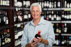 Smiling senior man choosing wine Stock Image