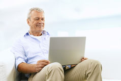 Smiling Senior Man On Couch Stock Photos