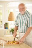 Smiling senior man cutting up pizza Royalty Free Stock Image