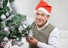 Smiling Senior Man Decorating Christmas Tree Royalty Free Stock Photos