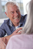 Smiling senior man drinking coffee and talking to wife Stock Photos