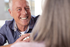 Smiling senior man drinking coffee and talking to wife Stock Images