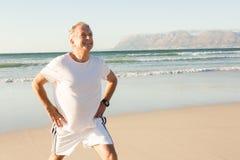 Smiling senior man exercising while standing on sand Royalty Free Stock Photo