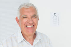 Smiling senior man with eye chart in the background Royalty Free Stock Photo