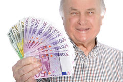 Smiling senior man with a fistful of money. Smiling senior man with a fistful of fanned 500 euro banknotes depicting wealth and security in old age through sound Stock Photos
