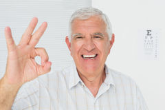 Smiling senior man gesturing ok with eye chart in background Royalty Free Stock Photography