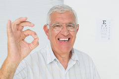 Smiling senior man gesturing ok with eye chart in background Royalty Free Stock Images