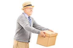 Smiling senior man giving a box to someone Royalty Free Stock Image