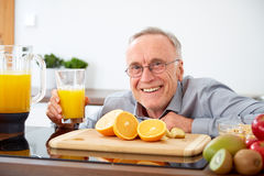 Smiling senior man with a glass of orange juice Royalty Free Stock Photo
