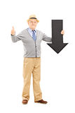 Smiling senior man holding an arrow pointing down and giving a t Royalty Free Stock Images