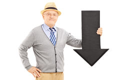 Smiling senior man holding a big black arrow pointing down royalty free stock photo