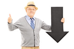 Smiling senior man holding a black arrow pointing down and giving a thumb up royalty free stock images