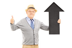 Smiling senior man holding a black arrow pointing up and giving Stock Image