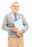 Smiling senior man holding a book Stock Photo