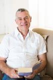 Smiling senior man holding book on sofa Royalty Free Stock Image
