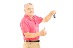 Smiling senior man holding a car key and giving thumb up Royalty Free Stock Photography