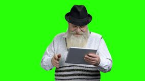 Smiling senior man holding computer tablet. Positive senior man waving with hand while holding portable tablet on green screen. Communication via internet stock video