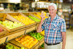 Smiling senior man holding orange stock image