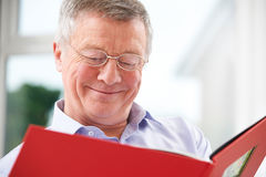 Smiling Senior Man Looking At Photo Album Royalty Free Stock Photo