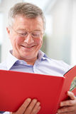 Smiling Senior Man Looking At Photo Album Stock Images