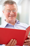 Smiling Senior Man Looking At Photo Album Royalty Free Stock Photography