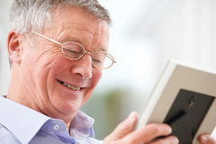 Smiling Senior Man Looking At Photograph In Frame Stock Photos