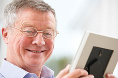Smiling Senior Man Looking At Photograph In Frame Stock Image