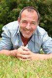 Smiling senior man lying in grass Royalty Free Stock Photo