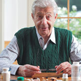 Smiling senior man with many pills stock image