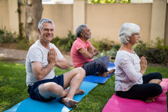 Smiling senior man meditating in prayer position with friends Stock Photos
