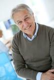 Smiling senior man at office stock photos