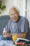 Smiling Senior Man With Orange Juice Royalty Free Stock Photography
