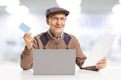 Smiling senior man paying bills with a credit card online on a laptop computer royalty free stock image