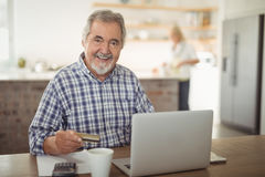 Smiling senior man paying bills online on laptop in kitchen stock image